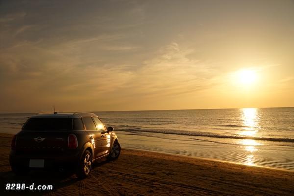 海に沈む夕日とオレンジ色に染まるMINIクロスオーバー